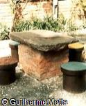 Mesa e assentos em concreto, tijolo e pedra